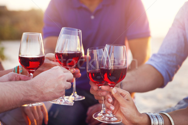 People holding glasses of red wine making a toast at the beach  Stock photo © dashapetrenko