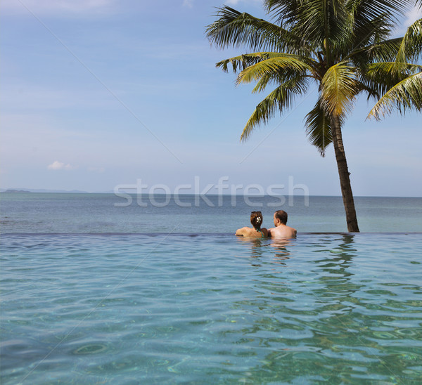 Young couple relaxing in infinity pool under coco palms Stock photo © dashapetrenko