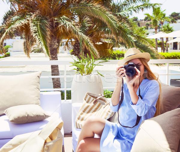 Happy young blond woman taking photo with camera Stock photo © dashapetrenko