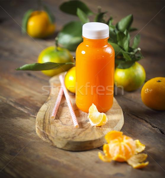 Um garrafa fresco tangerina suco maduro Foto stock © dashapetrenko