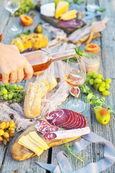 Picnic with rose wine fruits meat and cheese Stock photo © dashapetrenko