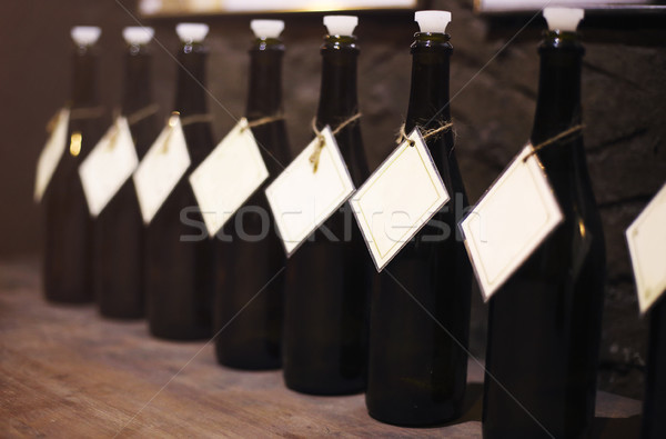 Wine bottles in the row on wooden table Stock photo © dashapetrenko