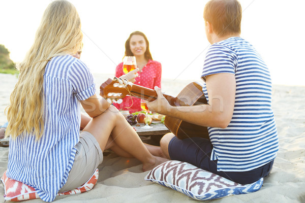 Stock photo: Young friends drinking rose wine on summer beach picnic
