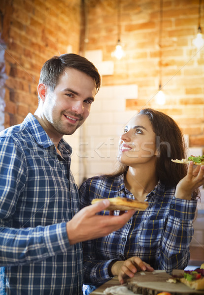 Stock photo: Young man and woman cooking and eating together at kitchen