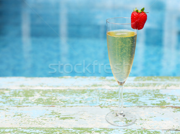 Champagne glass with strawberry on turquiose background Stock photo © dashapetrenko