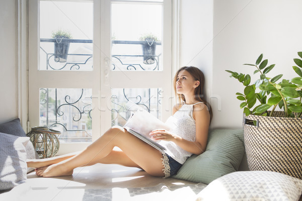 Young pretty girl reading fashion magazine near window Stock photo © dashapetrenko