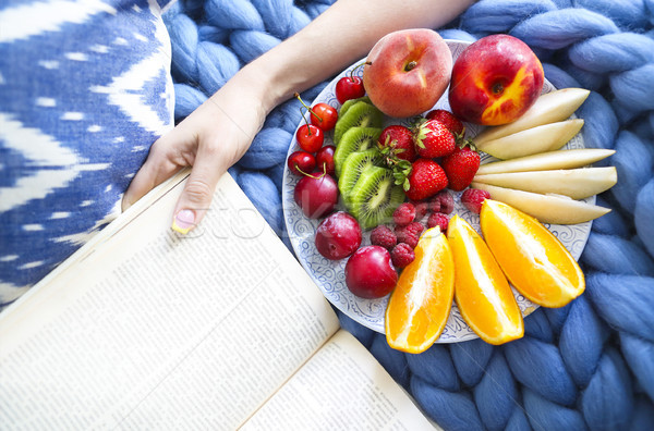 Plate with fresh fruit salad on a blue plaid with book  Stock photo © dashapetrenko