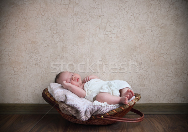 Baby sleeping in the basket on the wooden floor Stock photo © dashapetrenko
