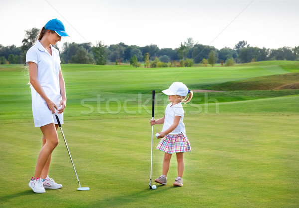 Mother and daughter practicing to hit the ball at the course Stock photo © dashapetrenko