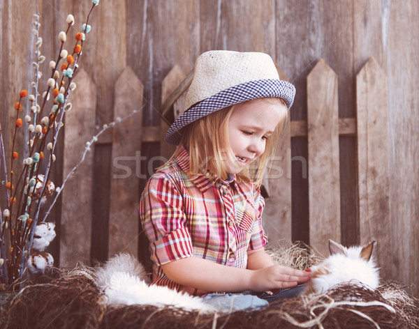 Portrait of an adorable baby girl and little white rabbit near t Stock photo © dashapetrenko