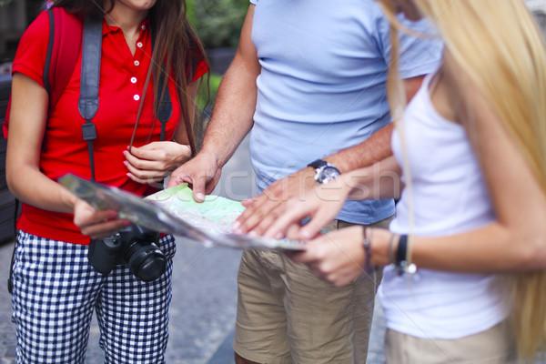 Three tourist looking at map in the street Stock photo © dashapetrenko