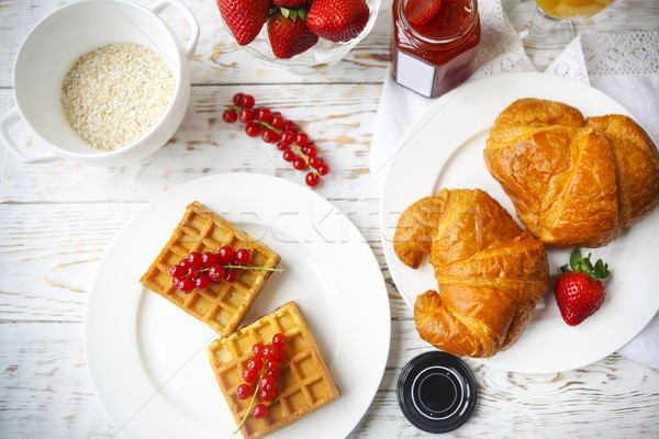 Waffles with red currant jam and berries, croissants, orange jui Stock photo © dashapetrenko