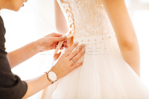 Bridesmaid helping the bride to put her wedding dress on Stock photo © dashapetrenko