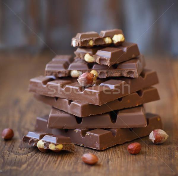 Broken chocolate bars and hazelnuts (filbert) on wooden table Stock photo © dashapetrenko