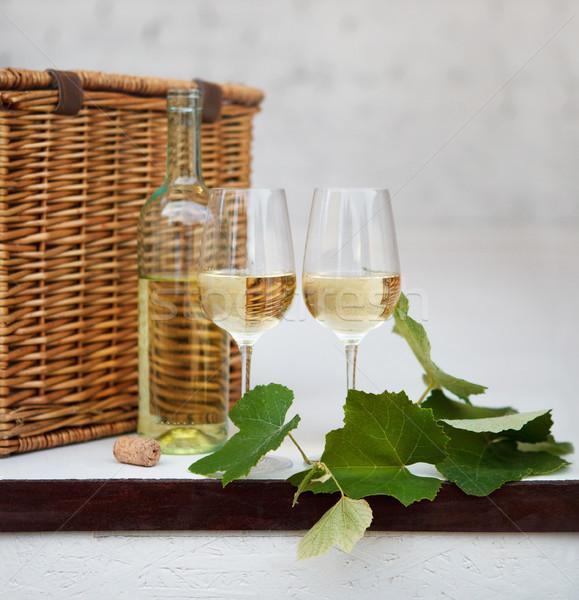 Still life with glasses of white wine, bottle, basket Stock photo © dashapetrenko