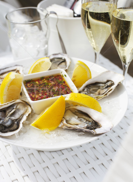 Fresh oysters shell with lemon and glasses of champagne Stock photo © dashapetrenko