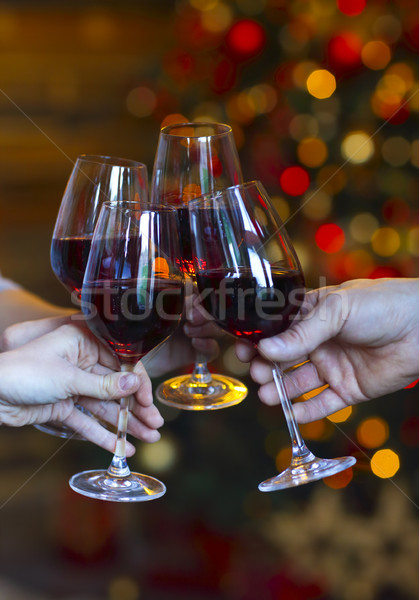 Clinking glasses of wine in hands on bright christmas lights bac Stock photo © dashapetrenko