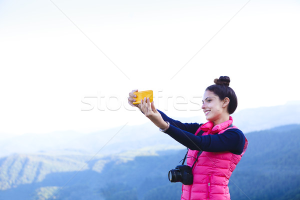 Woman hiker taking photo with smart phone at mountain peak Stock photo © dashapetrenko