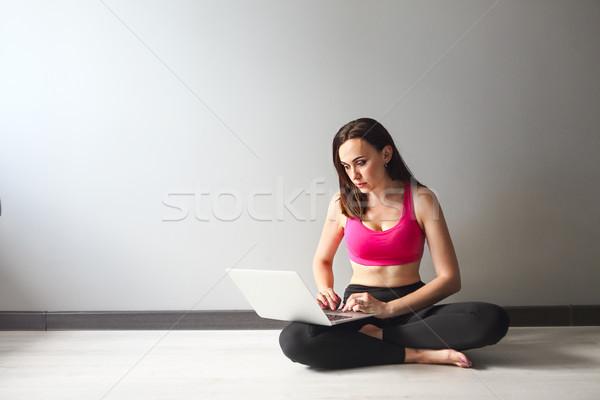 Sporty young brunette woman using laptop Stock photo © dashapetrenko