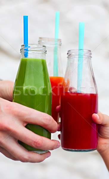 Family of three clinking glasses with fresh multicolored juice Stock photo © dashapetrenko