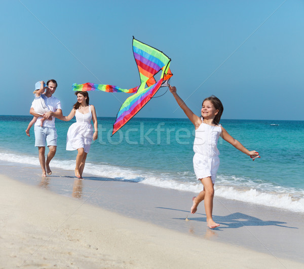 Happy young family with flying a kite  Stock photo © dashapetrenko