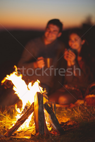 Portrait of the happy couple sitting by fire on autumn beach at  Stock photo © dashapetrenko