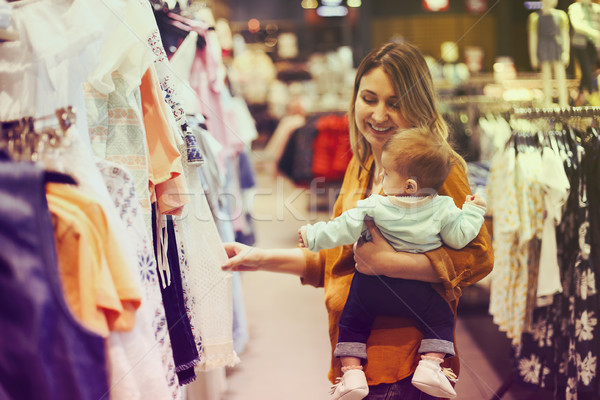 Blonde woman with little daughter in clothes store Stock photo © dashapetrenko