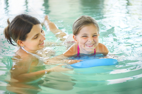 Mother learning to swim her little daughter in an indoor swimmin Stock photo © dashapetrenko
