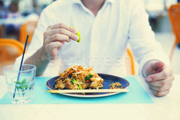 Man at thai restaurant eating pad thai Stock photo © dashapetrenko