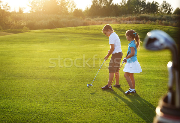 Casual kids at a golf field holding golf clubs Stock photo © dashapetrenko