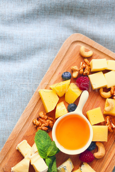 Cheese, honey, berries and nuts on wodden board Stock photo © dashapetrenko