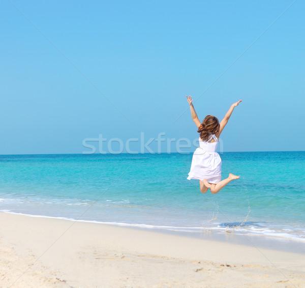 Woman in white dress jumping on the beach Stock photo © dashapetrenko