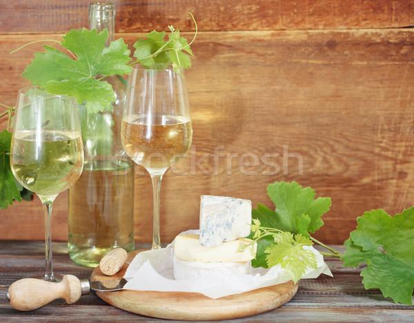 Glasses of white wine, bottle and cheese Stock photo © dashapetrenko