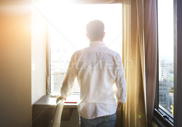 Rear view of young man looking at dawn city scenery in window af Stock photo © dashapetrenko