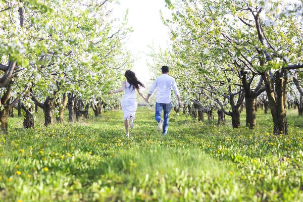 Young couple in love running in spring blossom garden Stock photo © dashapetrenko