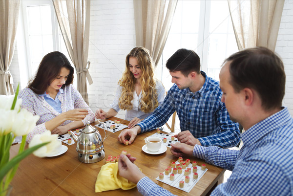 Happy young friends playing board game together  Stock photo © dashapetrenko