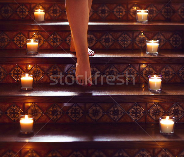 Woman on the stairs. Burning small candles in glasses, romantic  Stock photo © dashapetrenko