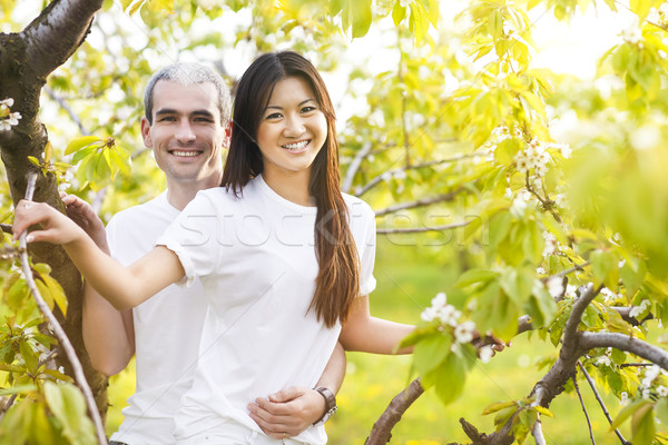Happy smiling couple in love in spring garden Stock photo © dashapetrenko