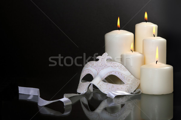 Stock photo: Candles and carnival mask over black background