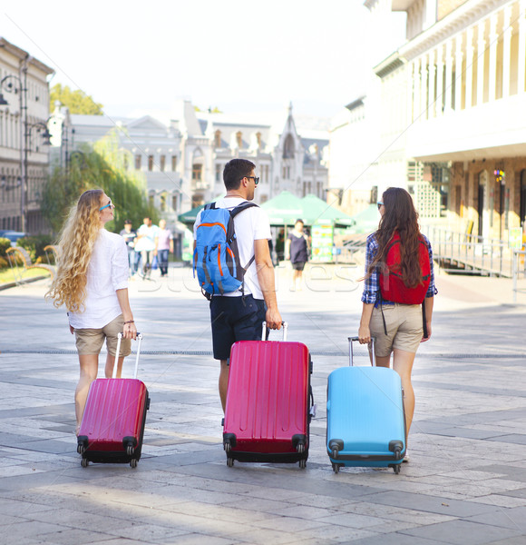 Travelers friends with luggage walking by street in the city Stock photo © dashapetrenko