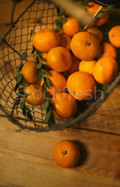 Basket of tangerines on a wooden table Stock photo © dashapetrenko