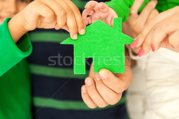 Family of four holding green house in hands Stock photo © dashapetrenko