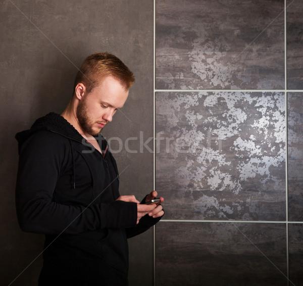 Lezser férfi érintőképernyő telefon szürke fal Stock fotó © dashapetrenko