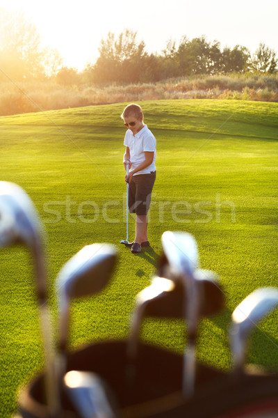 Casual kid at a golf field holding golf club Stock photo © dashapetrenko