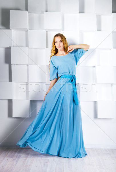 Stock photo: Beautiful blond woman in long dress near the white wall