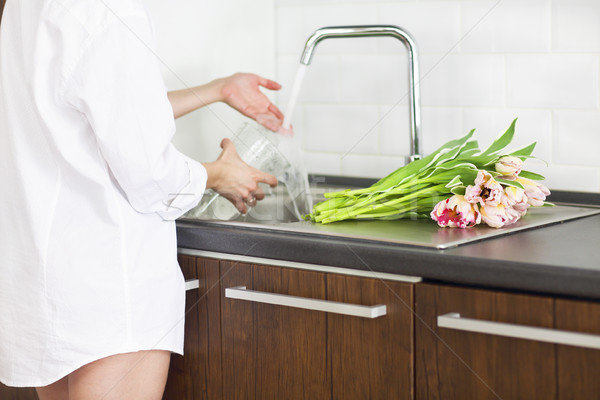 Young woman rinsing and cutting flowers and pouring water into t Stock photo © dashapetrenko