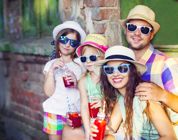 Happy young family in the street wearing hats and sunglasses Stock photo © dashapetrenko