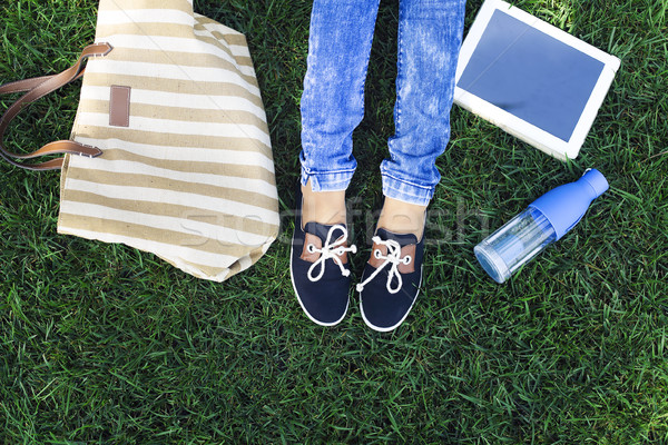 Feet of a young girl on a background a green grass with bottle o Stock photo © dashapetrenko