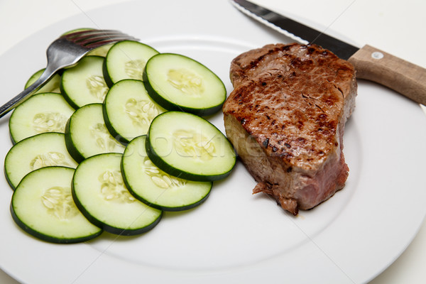 Steak and Cucumbers with knife and fork Stock photo © dbvirago