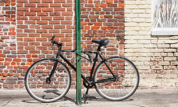 Black Bike Chained to Green Post Stock photo © dbvirago